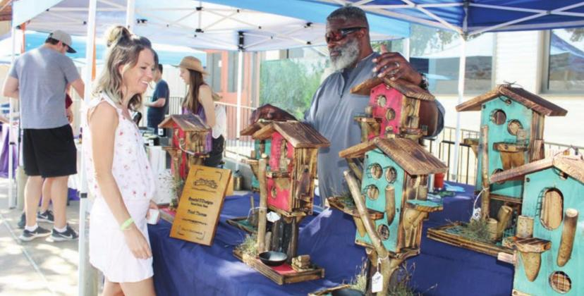 Horseshoe Bay resident Stephanie DeVault admired the custom-made birdhouses offered by Floyd Thomas during the Open Air Market June 13 in Old Oak Square in Marble Falls. Photos by Connie Swinney/The Highlander