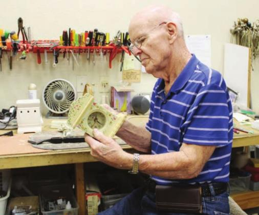"Above:Frank Crow has worked for several years repairing donated items including clocks and other household goods for sale to thrift store customers. ""It's a great place to work because of the people,"" he said. Photos by Connie Swinney/The Highlander"