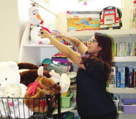 Celeste Munoz organized some of the displays Nov. 10 and placement of toys, babies and children's apparel as well as some household items. Connie Swinney/The Highlander