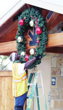 Workers, including city worker Robert Beard (above), assisted with the installation of decorations Nov. 9 on downtown amenities and US 281 light fixtures (right). Photos by Connie Swinney/The Highlander