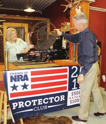 Burnet County Friends of NRA event committee members Pat Pucik and Mark McDonald unveiled live auction items Aug. 6 for an upcoming fundraiser, which had been postponed in the spring during COVID-19 venue closures. Connie Swinney/The Highlander