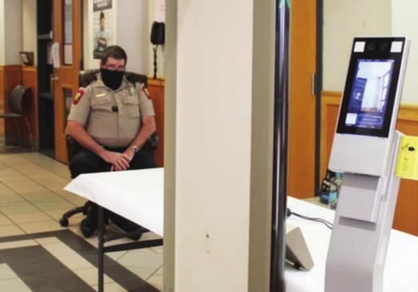 Burnet County Sheriff's Office Deputy Jim Prew, seen here on Jan. 26, is among law enforcement on shifts who monitor a kiosk that records whether a visitor is wearing a face covering and takes temperatures at the courthouse south annex doorway. Connie Swinney/The Highlander