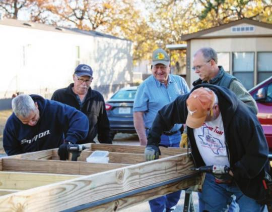 The Texas Ramp Project provided the labor to install a wheelchair ramp for an elderly couple at their home at 115 Happy Oaks, Kingsland, on Thursday, Dec. 10. Left: Robert Thiesen, Richard Lewis, Wayne Davis, Alan McCaleb and Dave Zinnecker of the Texas Ramp Project work on the base of a ramp for a Kingsland couple.