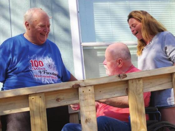 Don Barlow, left, shows William Proctor, center, and his daughter, Joni, the new ramp the Texas Ramp Project built at the Proctor home in Kingsland on Thursday, Dec. 10.