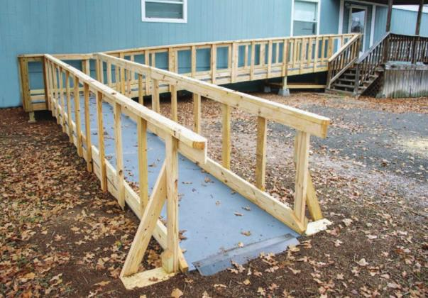 Ramp Revamp: Workers with The Texas Ramp Project install a wheelchair ramp for an elderly couple at their home at 115 Happy Oaks in Kingsland.
