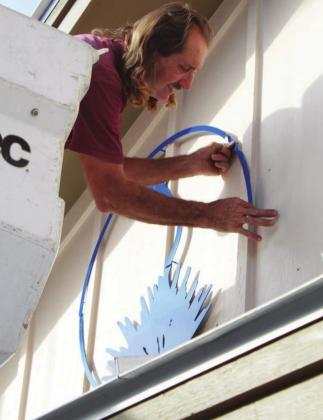John Davis installs the iconic century plant logo of The Highlander on the front of the newspaper office at 905 Third St., Marble Falls, on Tuesday, Oct. 13. The sign was custom built by Signs2Go. Lew K. Cohn/The Highlander